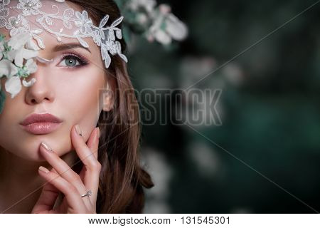 Portrait of a beautiful fashion bride wedding dress sweet and sensual . Wedding makeup and hair . Flowers background. Art in a contemporary style . Blue eyes. Against the background of blooming apple orchards .