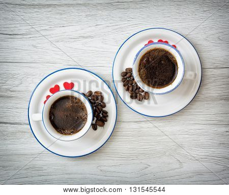 Two ceramic cups of coffee with little red hearts on the wooden background. Coffee beans. Stylish still life. Refreshment theme. Valentine's Day. Love theme.