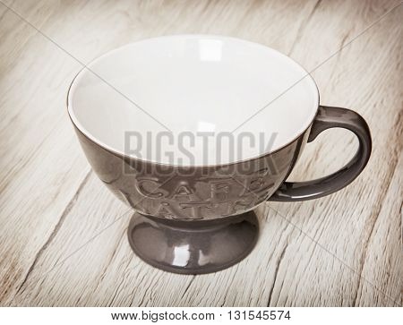 Grey cup with handle for coffee latte on the wooden background. Stylish empty cup. Kitchen utensil Cup with tab. Symbolic object.