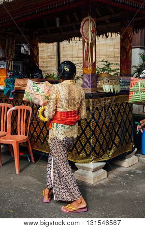 UBUD INDONESIA - MARCH 02: Balinese woman in traditional clothes with ceremonial box for offerings during Balinese New Year or Nyepi Day celebrations on March 02 2016 in Ubud Bali.
