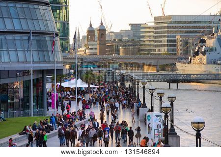 LONDON, UK - SEPTEMBER 19, 2015: South bank of river Thames in sun set light. View includes a lot of walking people