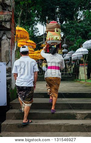 UBUD INDONESIA - MARCH 02: Balinese man and woman in traditional clothes going to the temple during Balinese New Year or Nyepi Day celebrations on March 02 2016 in Ubud Bali.