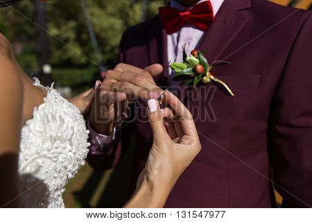 groom wears the ring bride at a wedding ceremony outdoors