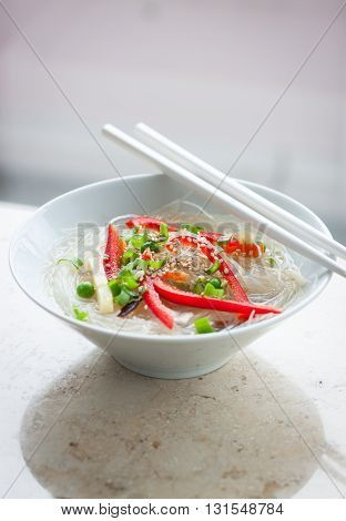 Asian rice noodles with vegetables and sesame in a bowl on a marble background closeup