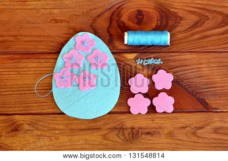 Felt Easter egg with flowers on a brown wooden background. Sew the flowers to the felt egg. Sewing set