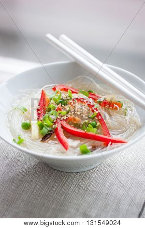 Asian rice noodles with vegetables and sesame in a bowl on a linen textile background closeup selective focus