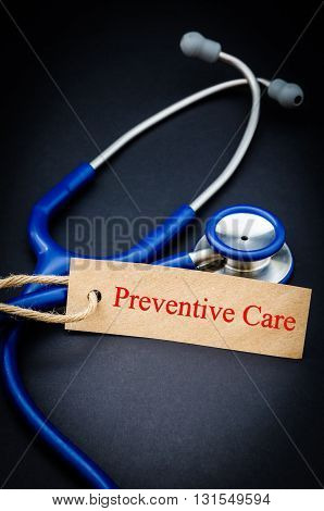 Preventive care in paper tag with stethoscope on black background - health concept. Medical conceptual