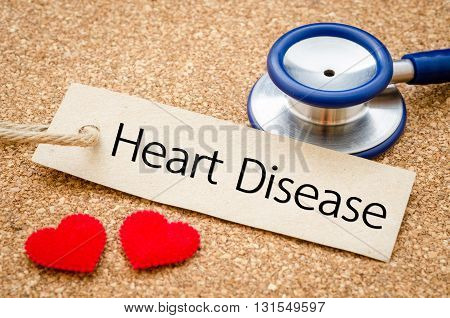Heart desease word in paper tag with red heart and stethoscope on wood table. Medical concept.