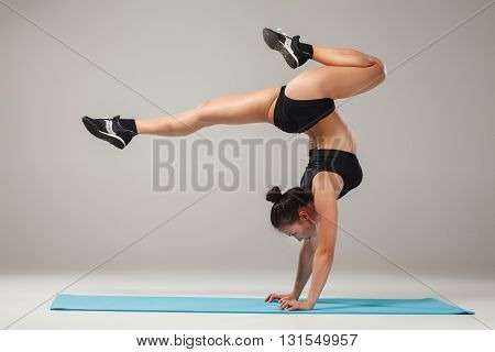Beautiful sporty girl standing in acrobat pose or yoga asana on gray background