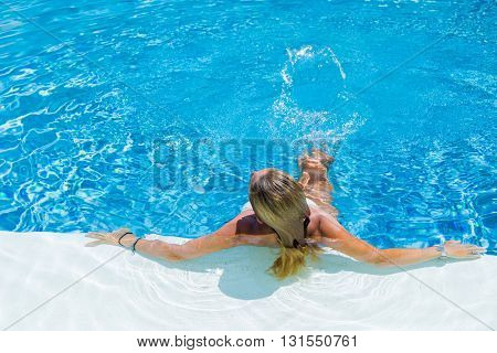 Unrecognizable woman relaxing at the swimming pool