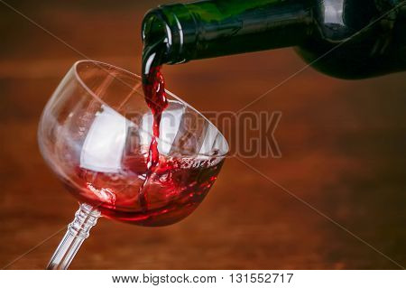 Pouring red wine from green bottle into elegant glass on a dark wood background.