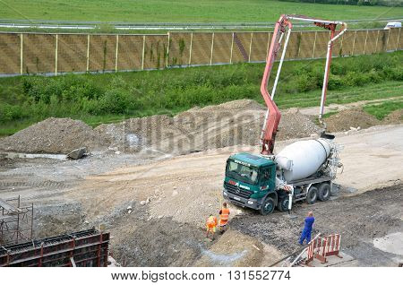 Dolny Hricov, Slovakia - May 20, 2016: Three workers and concrete transport truck with concrete pump ready for use. This activity is related to railway reconstruction process.