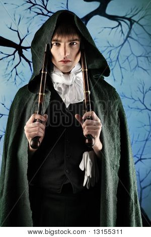 Portrait of a young gentlemen in a dinner jacket and cloak holding guns in his hands. Shot in a studio.