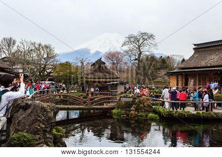 Oshino Japan - April 12 2016: Tourists visit Oshino Hakkai a small village in the Fuji Five Lake region located between Lake Kawaguchiko and Lake Yamanakako.