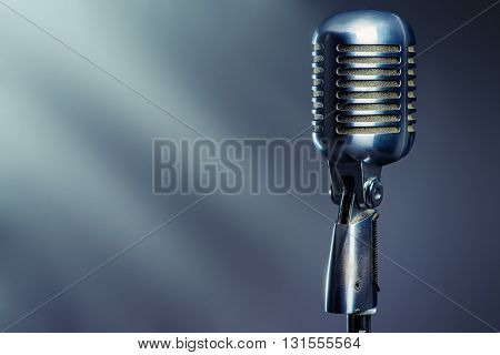 Vintage silver microphone over gray background.