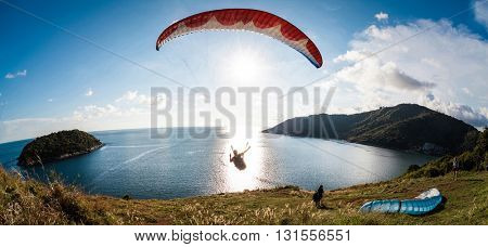 Paraglider flying over the water during sunset with the mountains