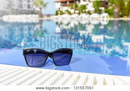 Beautiful sunglasses by the pool lying in the water.