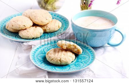 Coconut crunchy cookies on blue plate and cappuccino