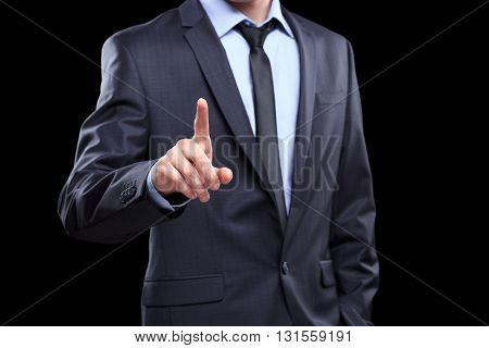 Business Man pushing on a touch screen interface. Black background