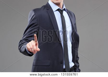 Business Man pushing on a touch screen interface. gray background