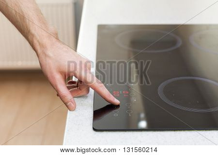 Close Up Of Hand Setting Temperature Control On Ceramic Stove