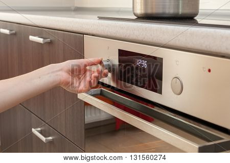 Close Up Of Women Hand Setting cooking mode on oven