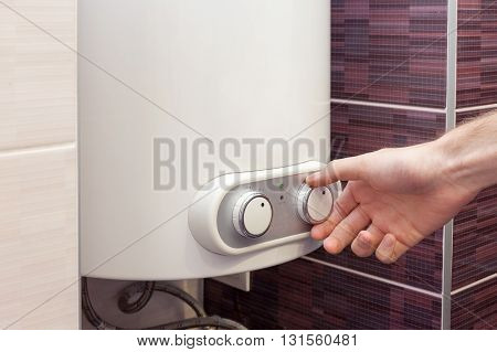 Close-up of man hands setting the temperature of water in Electric Boiler