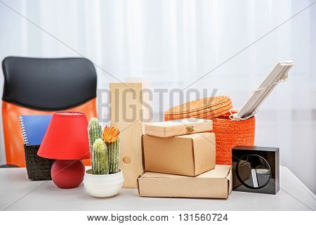 Wicker and cardboard boxes with things for relocation on light table