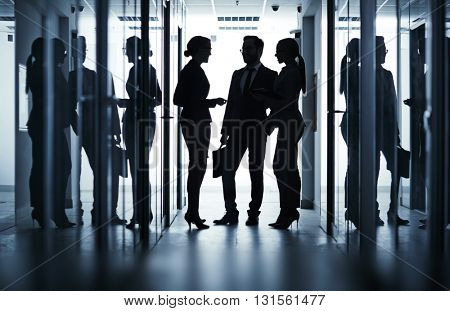 Silhouette of business team communicating in office corridor