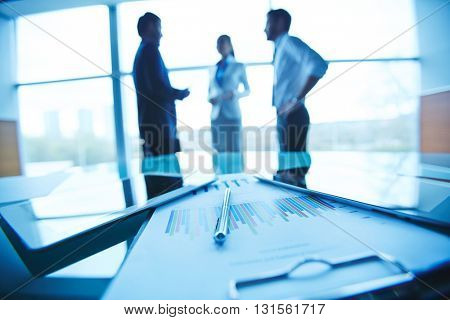 Financial report on the table with people standing in the background