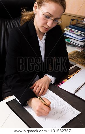 Attractive business woman working with documents in office. woman in a business suit sitting at a table and sign documents.