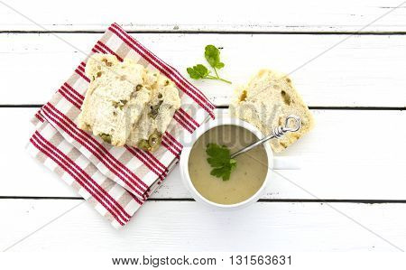 Chicken and Lemon Soup with olive bread on a white wooden table