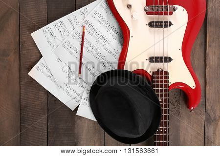 Electric guitar with notes and black hat on wooden background