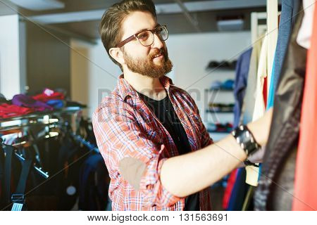 Young man choosing clothes in store