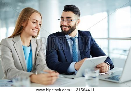 Man and woman discussing business questions presented on touchpad