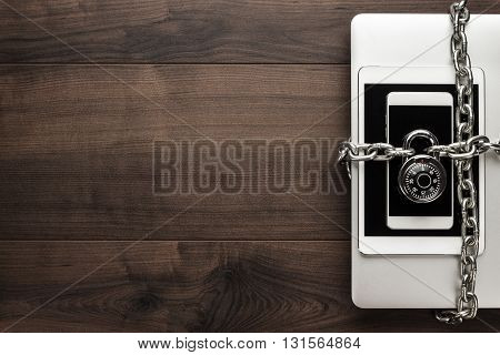 data security concept: computer, tablet, phone bound by metal chain and closed with combination lock on wooden table