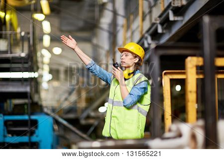Young female engineer talking on walkie talkie at factory