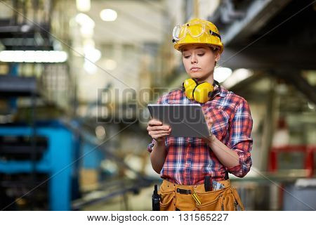 Young woman engineer checking production at factory