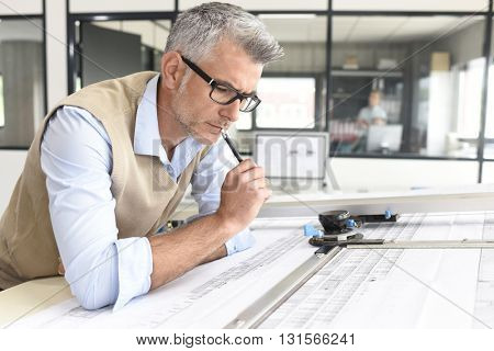 Architect sitting at drawing table in office