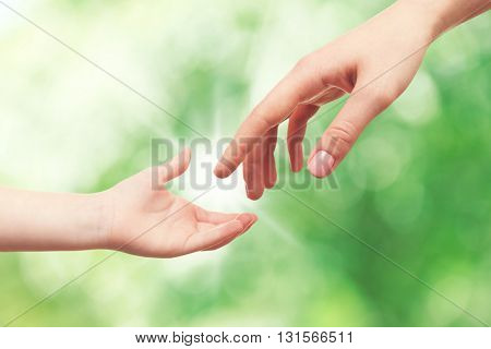 Child and mother hands on green nature background. Concept of taking care, protection, helping and assistance