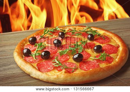 Tasty hot pizza with salami and olives on wooden table against fire flame background