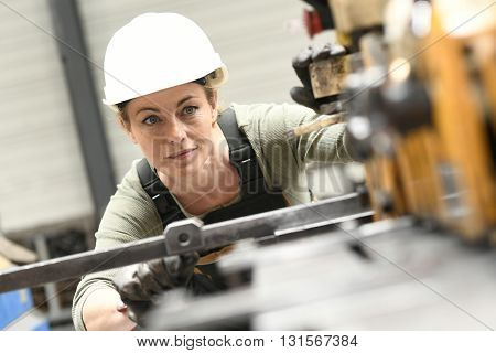Woman with helmet working in metallurgy factory