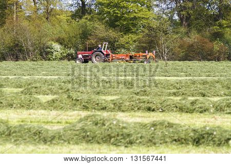LEUSDEN NETHERLANDS - MAY 6 2016: Farmer on tractor pulling a grass mower cutter through a lush green field on a spring day.