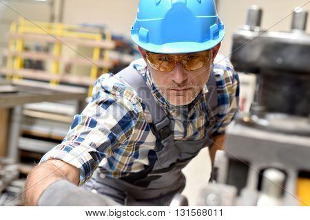 Metalworker with hardhat working on machine