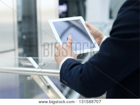 Midsection of businessman using digital tablet in office