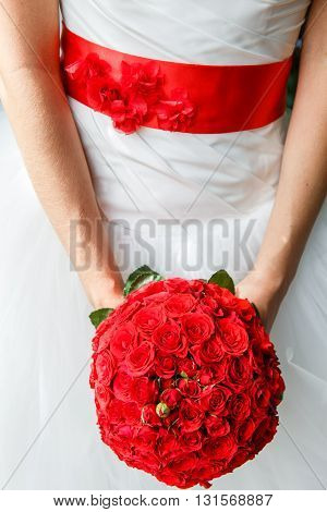 bouquet of red roses in bride's hands