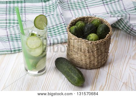 Summer cucumber cocktail and cucumbers in the basket on wooden desk.