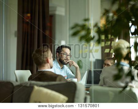 Young manager sitting at meeting with his colleagues