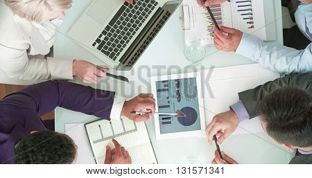 Business colleagues analyzing data on touchpad