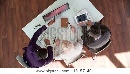 Three executives studying data on computer monitor